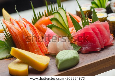A colorful platter of sashimi sushi with tuna and crab sticks in foreground and cucumber decorations - stock photo