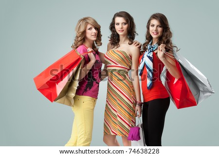 a colorful studio image of three beautiful young women standing, holding shopping bags and looking happy, smiling - stock photo