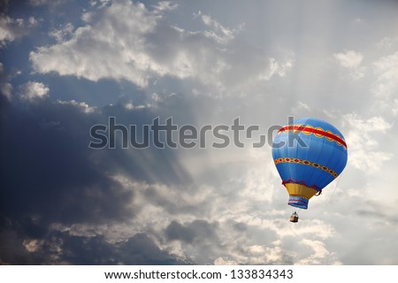 A colorful vintage hot air balloon floating in a surreal morning sky with sunshine bursting through the clouds. - stock photo