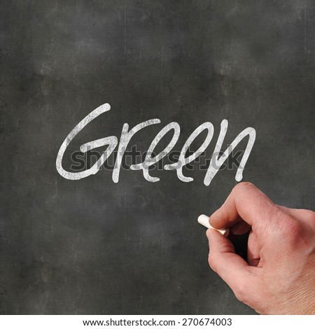 A Colourful 3d Rendered Concept Illustration showing a hand writting Green on a blank blackboard - stock photo