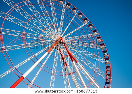 A colourful ferris wheel against a deep blue sky - stock photo