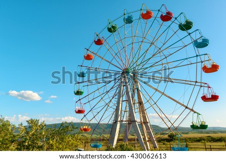A colourful ferris wheel on the background of blue sky - stock photo