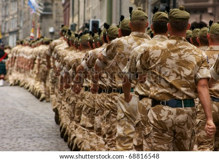 A column of British Army soldiers marching in desert camouflage. - stock photo