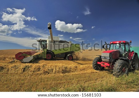 A combine harvester harvests wheat under a British summer sky. Space for text in the sky. - stock photo
