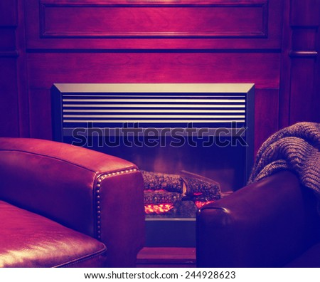 a comfortable cozy interior fireplace and cozy armchair in living room  of a living room space  toned with a retro vintage instagram filter effect - stock photo