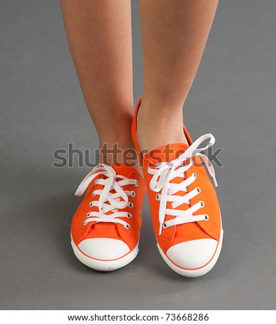 A comfortable woman sport shoe or sneaker in orange color - stock photo