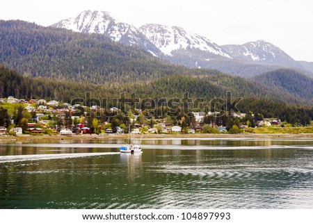 A commercial fishing boat cruising past colorful coastal homes in Alaska beneath majestic snow covered mountains - stock photo