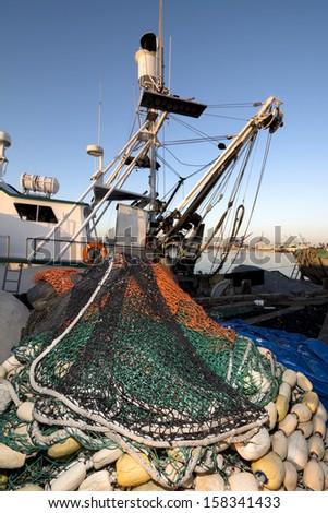 A commercial fishing boat with a purse sein net staged for a fishing trip  - stock photo