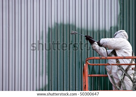 A commercial painter on an industrial lift spray painting a steel exterior wall or duct. - stock photo