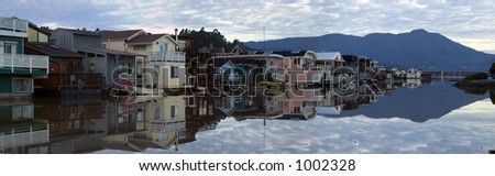 A community on the water in Sausalito, CA. Suburbia built on rafts, on a calm clear morning in late January. The bay is calm as glass, perfectly reflecting houses and Mt. Tamalpais. - stock photo