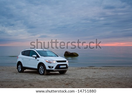 A compact SUV on a beach. Sunset. - stock photo