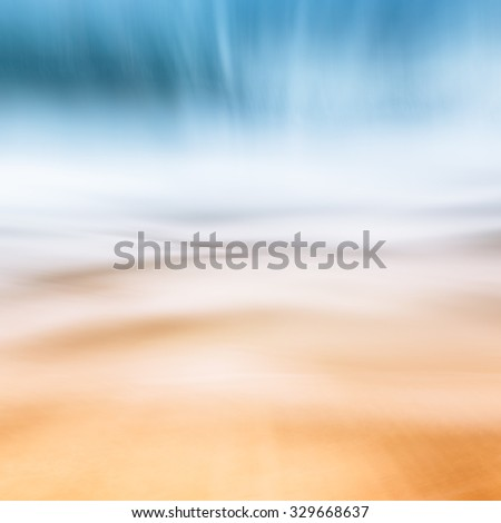 A complete abstraction of waves, sand, ocean and sky.  Image features a brown to blue color gradient. - stock photo