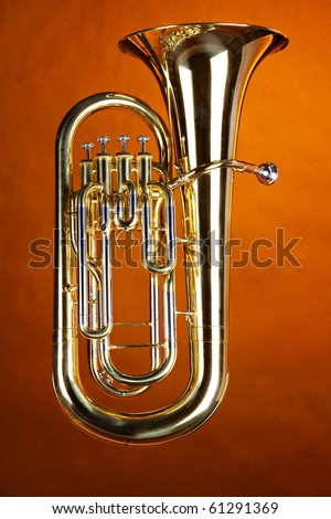 A complete gold brass tuba euphonium isolated against a spotlight gold background. - stock photo