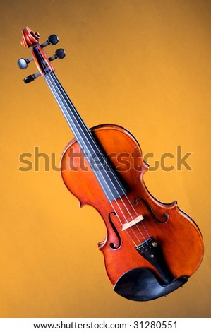 A complete violin viola isolated against a gold background in the vertical format with copy space. - stock photo