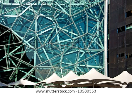 A complex arrangement of metal framework, behind a glass covered building in Melbourne, Australia - stock photo
