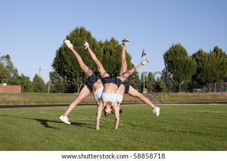 A composite of a female athlete performing a cartwheel on a grassy field. - stock photo