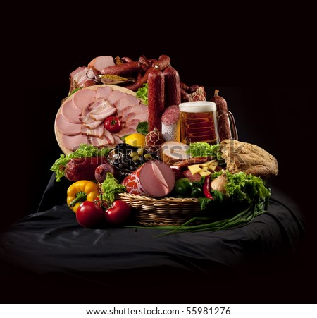 A composition of meat and vegetables with a pot full of beer on a black textile - stock photo
