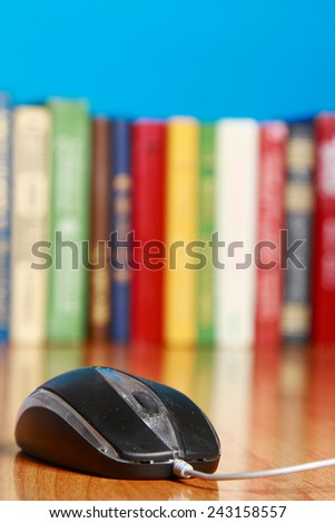 A computer mouse against books on the desk - stock photo