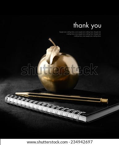 A concept image for rewards and success. A gold apple on a notebook with a gold pen against a black background. Copy space. - stock photo