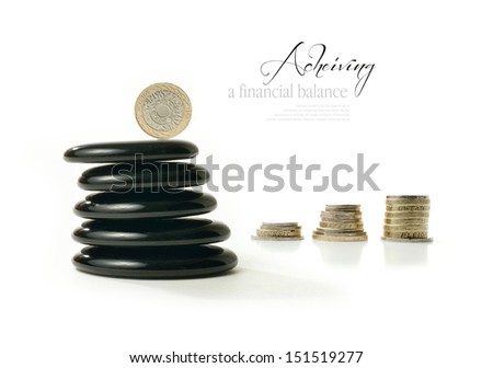 A concept image relating to financial matters. Balanced coin representing balance for investments, pension or savings with Feng Shui black stones. White background with copy space. - stock photo