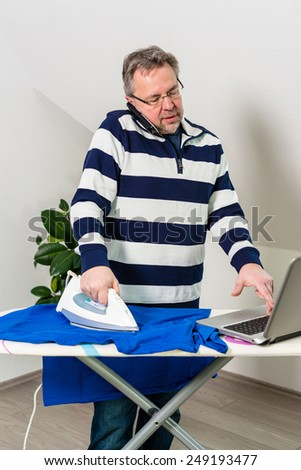A concept of a personal choice: work or family. Casual middle aged businessman doing housework and offce work at the same time - stock photo
