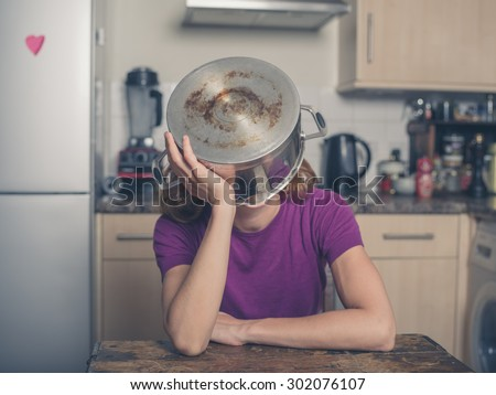 A concerned young woman is sitting at a table in a kitchen with a pot on her head - stock photo