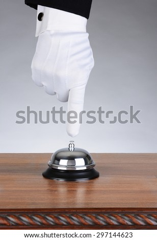 A concierge or Valet about to press the button of a service bell. The bell is on a wood desk with ornate scroll while the glove hand of the man is pointing straight down. - stock photo