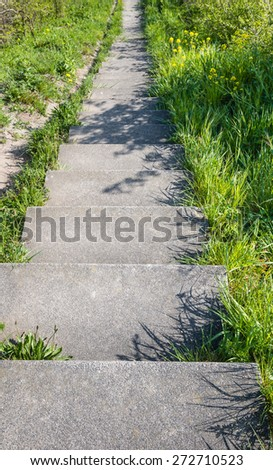 A concrete staircase between the grass and weeds seen from the top of a dike on a sunny day in the early spring season. - stock photo