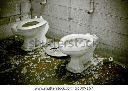 A condemned bathroom with dirty toilets in an abandoned warehouse factory. - stock photo