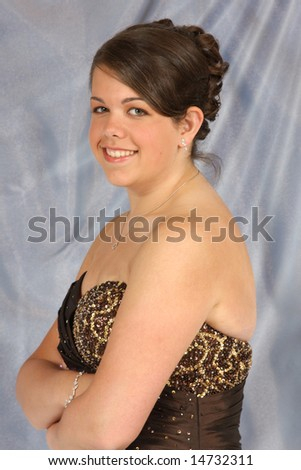 A confident, beautiful young woman dressed up in an evening gown. - stock photo
