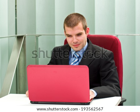 A confident businessman sitting in his office, in front of his laptop - stock photo