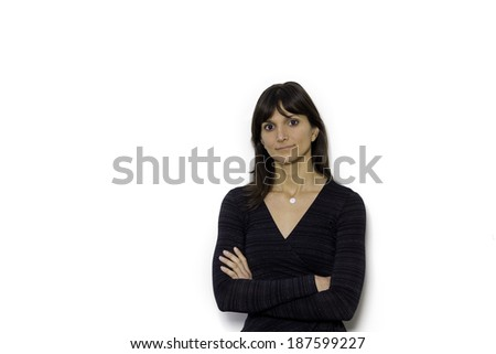 A confident, casual business woman smiling confidently with folded arms, Standing close to a white wall. - stock photo