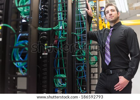 A confident data center manager posing in front of the data center equipment racks.  - stock photo