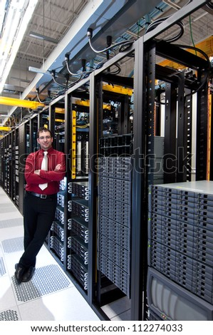 A confident datacenter manager looking at his datacenter equipment with a smile - stock photo