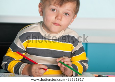 A confident little boy is sitting at the desk - stock photo