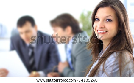 A confident relaxed business woman smiling with her colleagues at the back - stock photo