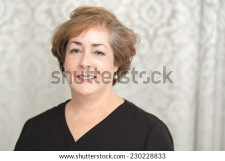 A confident smiling middle aged white woman with copy space on right. - stock photo