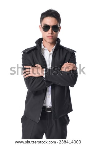 A confident young businessman stands in sunglasses with arms folded - stock photo