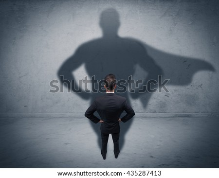 A confident young elegant salesman with briefcase facing a wall, looking at his superman shadow concept - stock photo