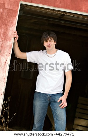 A confident young model posing outside a barn. - stock photo