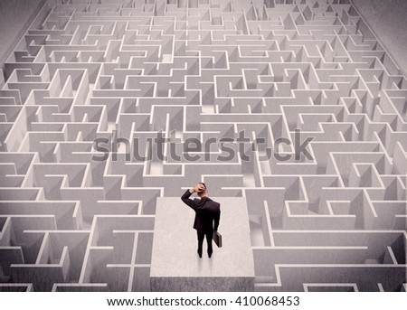 A confused businessman thinking while standing on a square platform above a detailed maze - stock photo