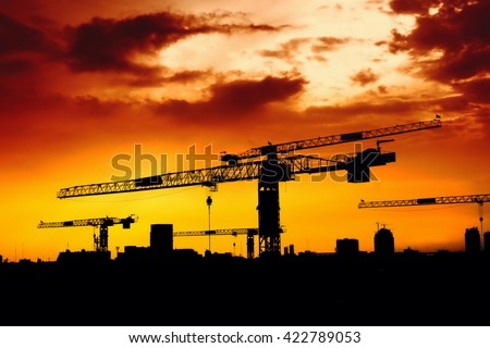 A construction crane silhouetted at sunset - stock photo