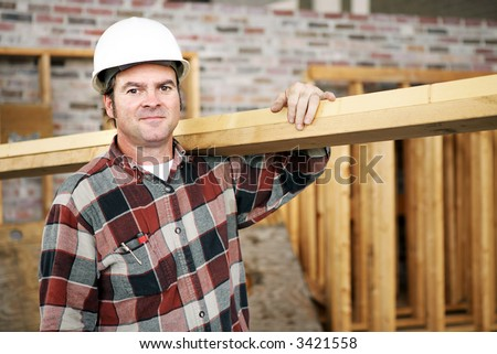 A construction day laborer carrying wood beams.  Authentic construction worker on an actual construction site. - stock photo