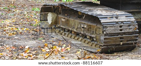A construction Excavator track resting on the ground outside in the woods with room for your text. - stock photo
