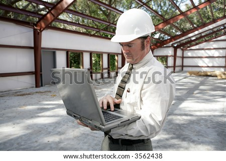 A construction inspector or engineer filling out his report on his laptop. - stock photo