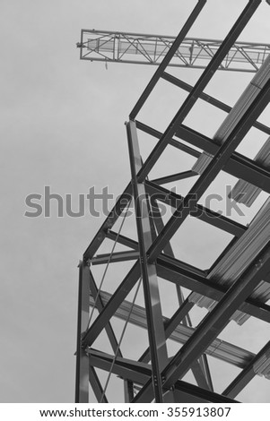 A construction site with steel framing and a yellow construction crane - stock photo
