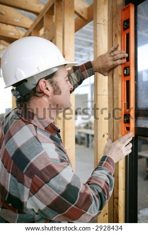 A construction worker checking that a newly installed window is level.  Vertical view.  Authentic and accurate content. - stock photo