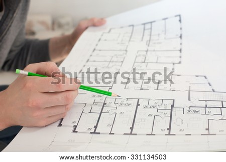 A construction worker on a construction site check documents with pencil in his hand - stock photo