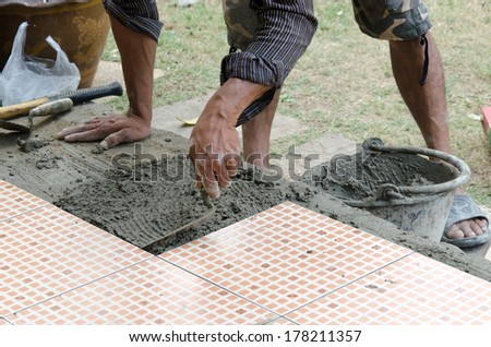 A construction worker putting on new floor tiles. - stock photo