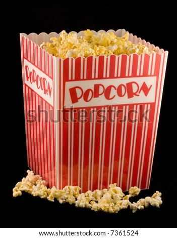 A container of popcorn isolated on a black background - stock photo
